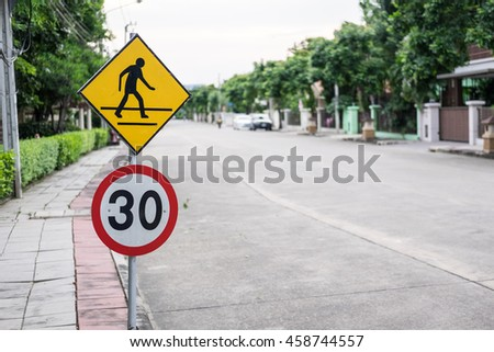 Bright yellow pedestrian crosswalk sign and speed limit sign on a street with traffic warning motorists to slow down for people crossing the street. - stock photo