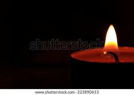 Brightly burning candle on a black background - stock photo
