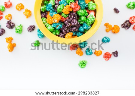 Brightly Colored Candied Popcorn, white background. Horizontal image of Junk food, fruit flavored popcorn in yellow bowl. Colorful, rainbow, candy coated popcorn. Shallow focus on popcorn in bowl - stock photo
