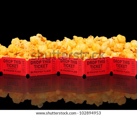 Brightly colored cheese corn on black with movie tickets - stock photo