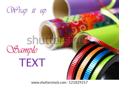 Brightly colored curling ribbon on spool with rolls of wrapping paper on white background with copy space.  Macro with shallow dof. - stock photo