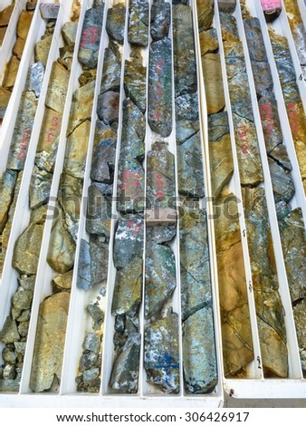 Brightly colored drill core logged in trays from epithermal gold and copper deposit. Australia. - stock photo