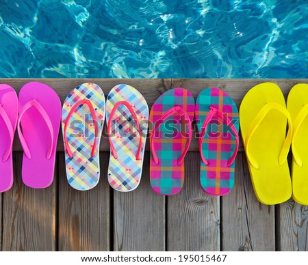 Brightly colored flip-flops on wooden background near the pool - stock photo