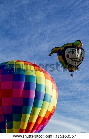 Brightly colored hot air balloon against blue morning sky on the ground before take off and joker head shaped balloon in the air - stock photo
