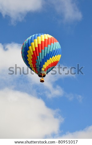 Brightly colored hot air balloon against cloudy blue sky - stock photo