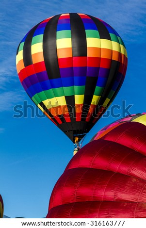 Brightly colored hot air balloons against blue morning sky on the ground and just after take off - stock photo