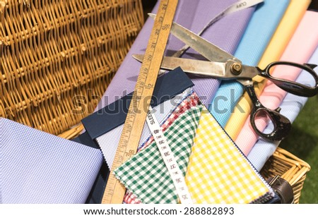 Brightly Colored Swatches in Wicker Basket with Wooden Rulers, Measuring Tape and Scissors - stock photo