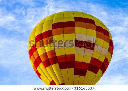 Brightly colored yellow and red hot air balloon against blue morning sky just after take off - stock photo