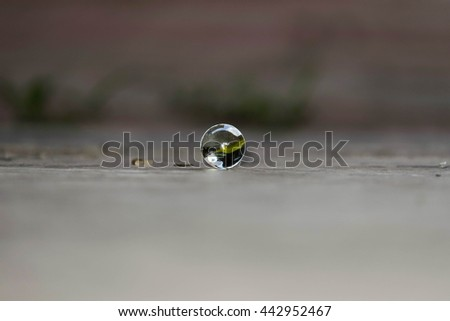 Brightly coloured glass marble with blurred background and low light - stock photo