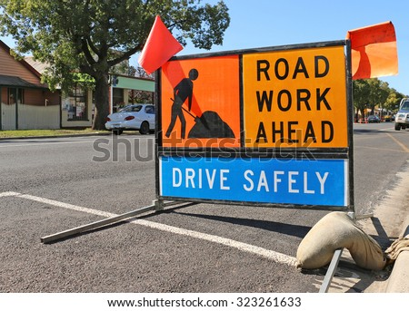 brightly coloured road work ahead signs - stock photo