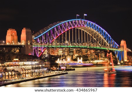 Brightly illuminated arch side of landmark Sydney Harbour Bridge after sunset reflecting lights in blurred still waters of bay. - stock photo