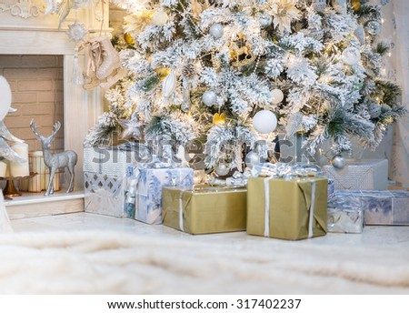 Brightly lit christmas tree with lots of gifts. - stock photo