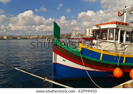 """Brightly painted fishing boats (""""luzzi"""") in harbor, on the island of Malta. The boats carry the """"Eyes of Osiris"""" to prevent ill-fortune. - stock photo"""
