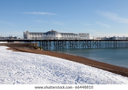 Brighton palace pier in winter. beach sea and victorian architecture covered in snow - stock photo