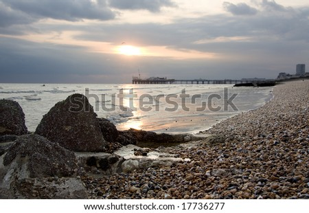 Brightonâ??s pebble beach at dusk Palace Pier in the background and mussel bank in the foreground - stock photo