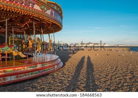 BRIGHTON, UK - July 27 2013: Two silhouettes of people standing next to a traditional carousel on Brightons famous beach as the sun goes down with the famous pier in the background. - stock photo