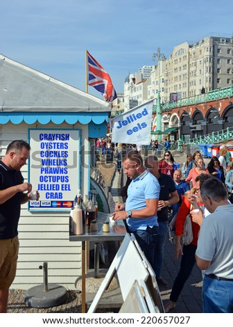 Brighton, United Kingdom - September 28, 2014: Tourists eat Jellied Eel on the beach on a Summer day at Brighton on the south coast of England. - stock photo