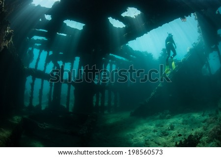 Brilliant beams of sunlight illuminate the remains of a shipwreck in the Solomon Islands. Many ships were sunk in this area during World War II. The wrecks now make artificial reefs. - stock photo