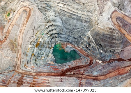 Brilliant colors explode in a vertical view of an open pit mining from above - stock photo