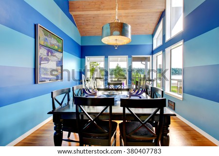 Brilliant dinning room with bright blue stripped walls. - stock photo