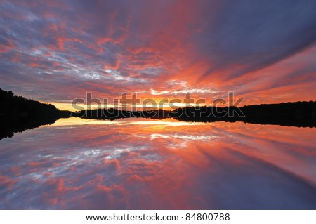 Brilliant red sunset and shoreline of West Lake with reflections in calm water, Michigan, USA - stock photo