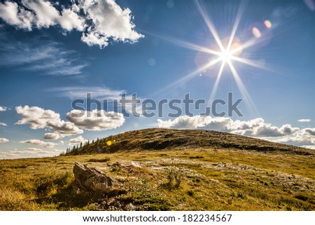 Brilliant sunburst over tundra in Alaska with blue sky and clouds. - stock photo