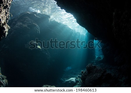 Brilliant sunlight penetrates a narrow crevice along the edge of a remote island in the Solomon Islands. This region is within the Coral Triangle and is known for its high marine habitat diversity. - stock photo