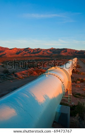 Brilliant sunrise lighting on a pipeline in the Mojave Desert. - stock photo