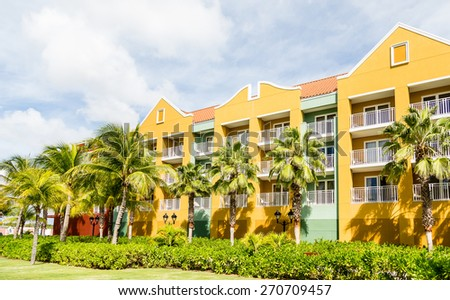 Brilliant yellow and green plaster resort beyond palm trees in Curacao - stock photo