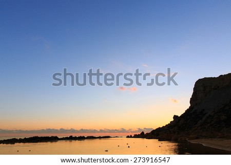 Brilliantly sunlit sky and clouds above calm surface of coastal waters in a secluded marine bay. Peacefulness, tranquility, remoteness, calm before the storm concept.  - stock photo