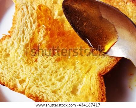 Brioche bread with honey spooned on - stock photo