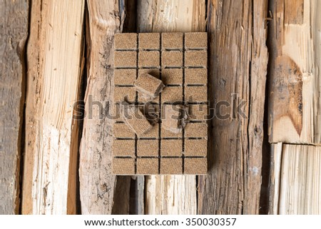 Briquettes for firing, ignition on the background of wood. View from above - stock photo