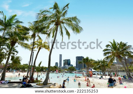 BRISBANE, AUS - SEP 25 2014:Visitors at Streets Beach in South Bank Parkland.It's Australia's only inner-city, man-made beach.It free to use and is patrolled by qualified lifeguards all year round. - stock photo