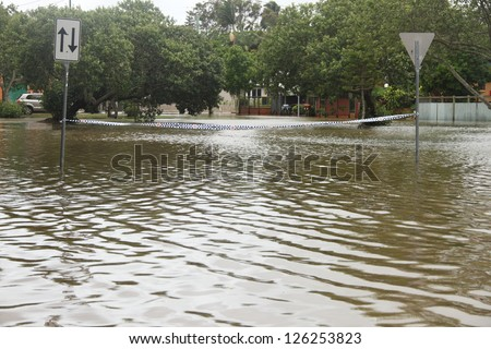 BRISBANE, AUSTRALIA - JANUARY 28 : Police tape accross flooded street from ex tropical cyclone Oswald on January 28, 2013 in Brisbane, Australia - stock photo