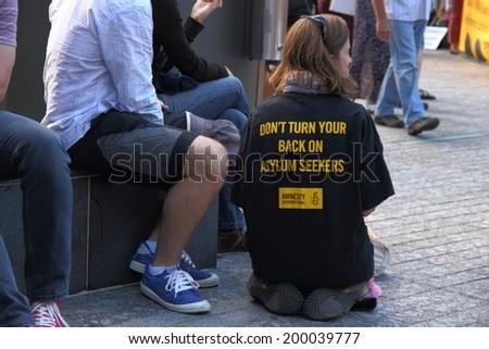 BRISBANE, AUSTRALIA - JUNE 22 : Unidentified protester wearing political shirt attending World Refugee Rally June 22, 2014 in Brisbane, Australia - stock photo