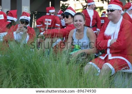 BRISBANE, AUSTRALIA  NOV 27 :Unidentified women spectator with unidentified santas before Variety Santa Fun Run November 27, 2011 in Brisbane, Australia - stock photo