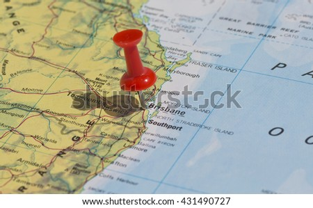 Brisbane marked on map with red pushpin. Selective focus on the word Brisbane and the pushpin. Pin is in an angle and casts some shadow to the left.  - stock photo