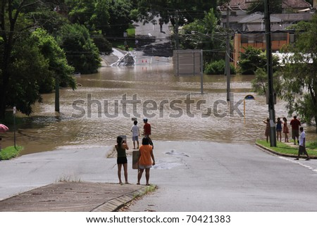 BRISBANE, QUEENSLAND/AUSTRALIA - JANUARY 13: People looking to flooded street on January 13, 2011 in St Lucia, Brisbane, Queensland, Australia. - stock photo