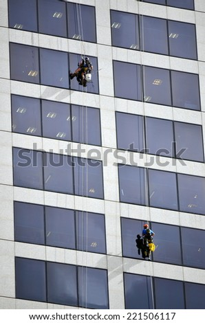 BRISBANE - SEP 25 2014:Window cleaners work on high rise building.Window cleaning is considered one of the most dangerous job in the world.Several window cleaners die each year and many are injured - stock photo