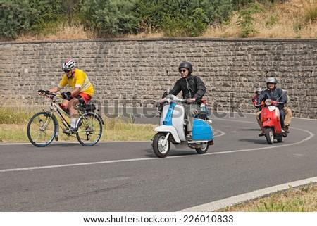 """BRISIGHELLA (RA), ITALY - JULY 7: unidentified bikers on a vintage italian scooters Lambretta and Vespa in rally """"Raduno auto e moto d'epoca"""" of Fognano, RA, on July 7, 2013 in Brisighella, RA, Italy  - stock photo"""