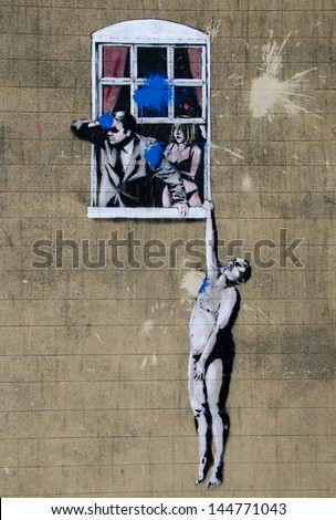 "BRISTOL, ENGLAND - JUL 3- 2006 - A mural named ""Naked Man"" by street artist Banksy on a wall in Park Street, Bristol on 3 Jul 2013. Painted in 2006 it is now firmly part of the Bristol tourist trail. - stock photo"