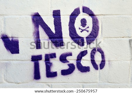 BRISTOL - NOV 8: View of a stencil graffiti piece with an anti Tesco theme on a city centre wall on Nov 8, 2010 in Bristol, UK. Small shops and business allege Tesco undercut prices. - stock photo