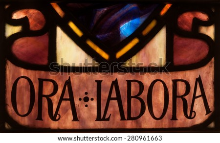 """BRISTOW, VIRGINIA - APRIL 26: Detail of stained glass window depicting the Benedictine motto, """"Ora et Labora"""" - """"prayer and work"""" - in chapel of St. Benedict Monastery - stock photo"""