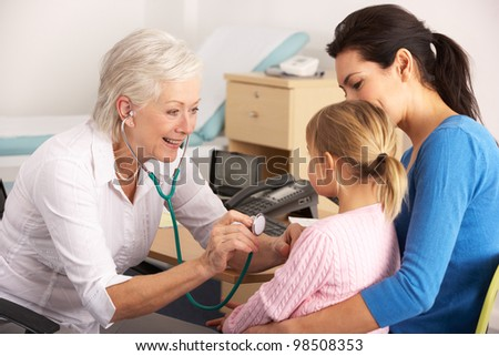 British GP examining young child with mother - stock photo