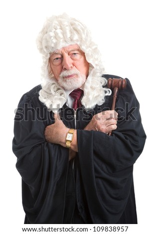 British judge in a wig, with his arms crossed looking stern, serious, and angry.  Isolated on white. - stock photo