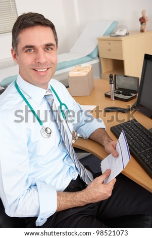 British male GP sitting at desk - stock photo