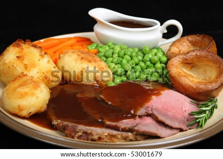 British roast beef dinner with Yorkshire puddings. - stock photo
