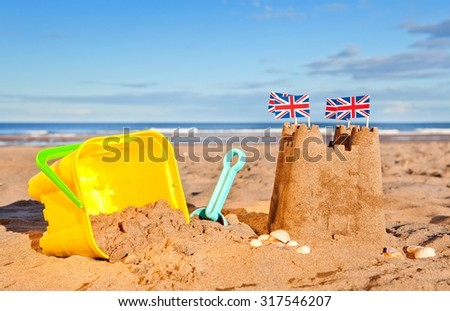 British Seaside traditional sand castle on the beach with bucket and spade shells and Union Jack Flags - stock photo