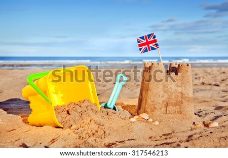 British Seaside traditional sand castle on the beach with bucket and spade shells and Union Jack Flag - stock photo