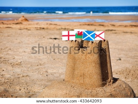 British seaside traditional sandcastle on the beach with regional flags. - stock photo
